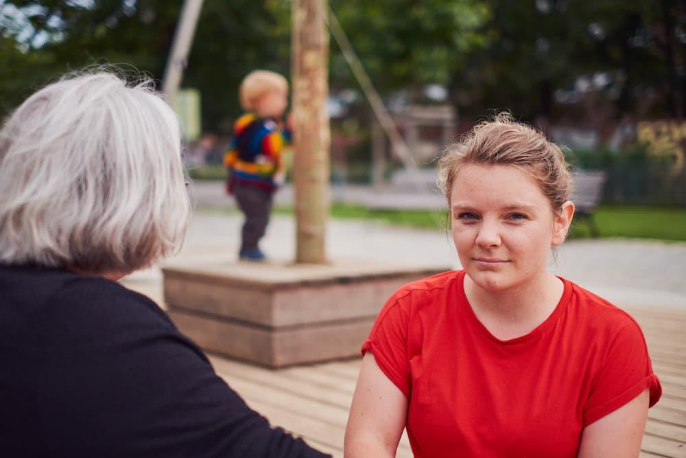 Marit Schatzmann fragend gegenüber einer grauhaarigen Person, im Hintergrund unscharf ein Kleinkind