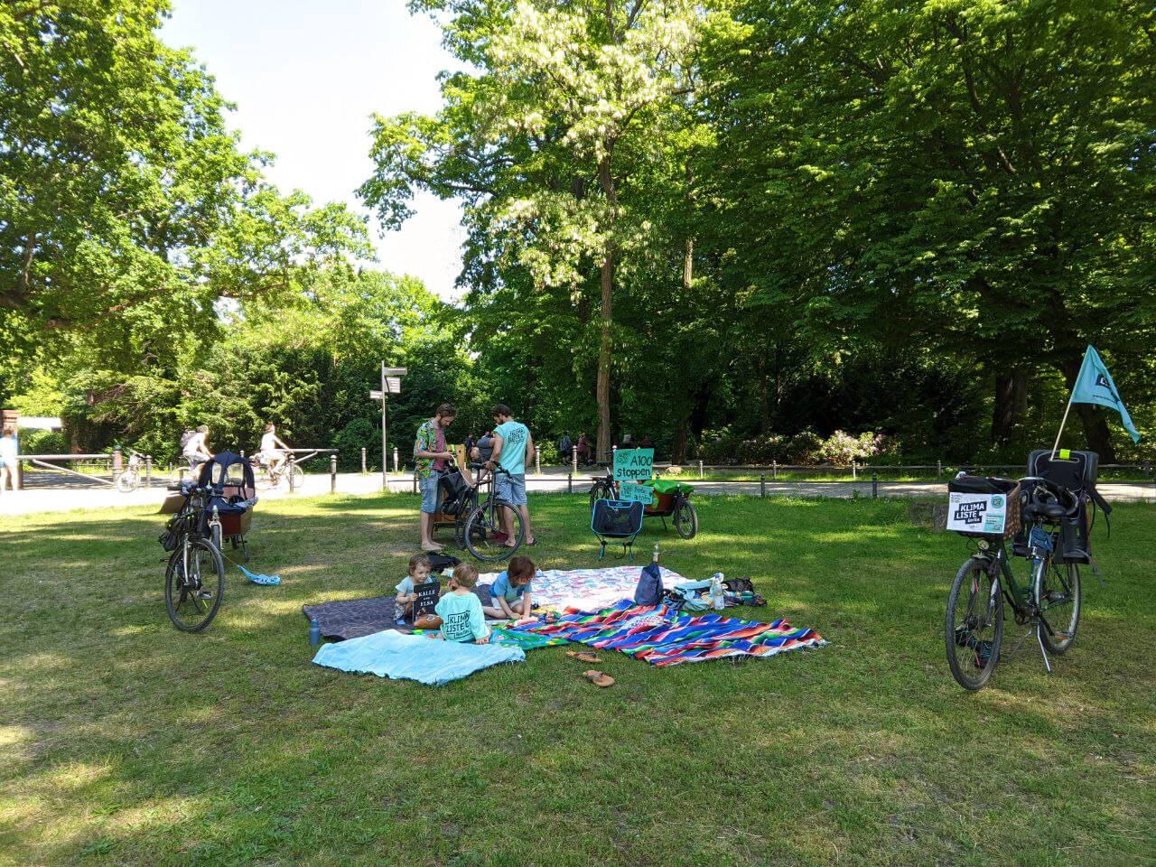 Eltern und Kinder mit Klimalisten-Shirts sitzen im Park.