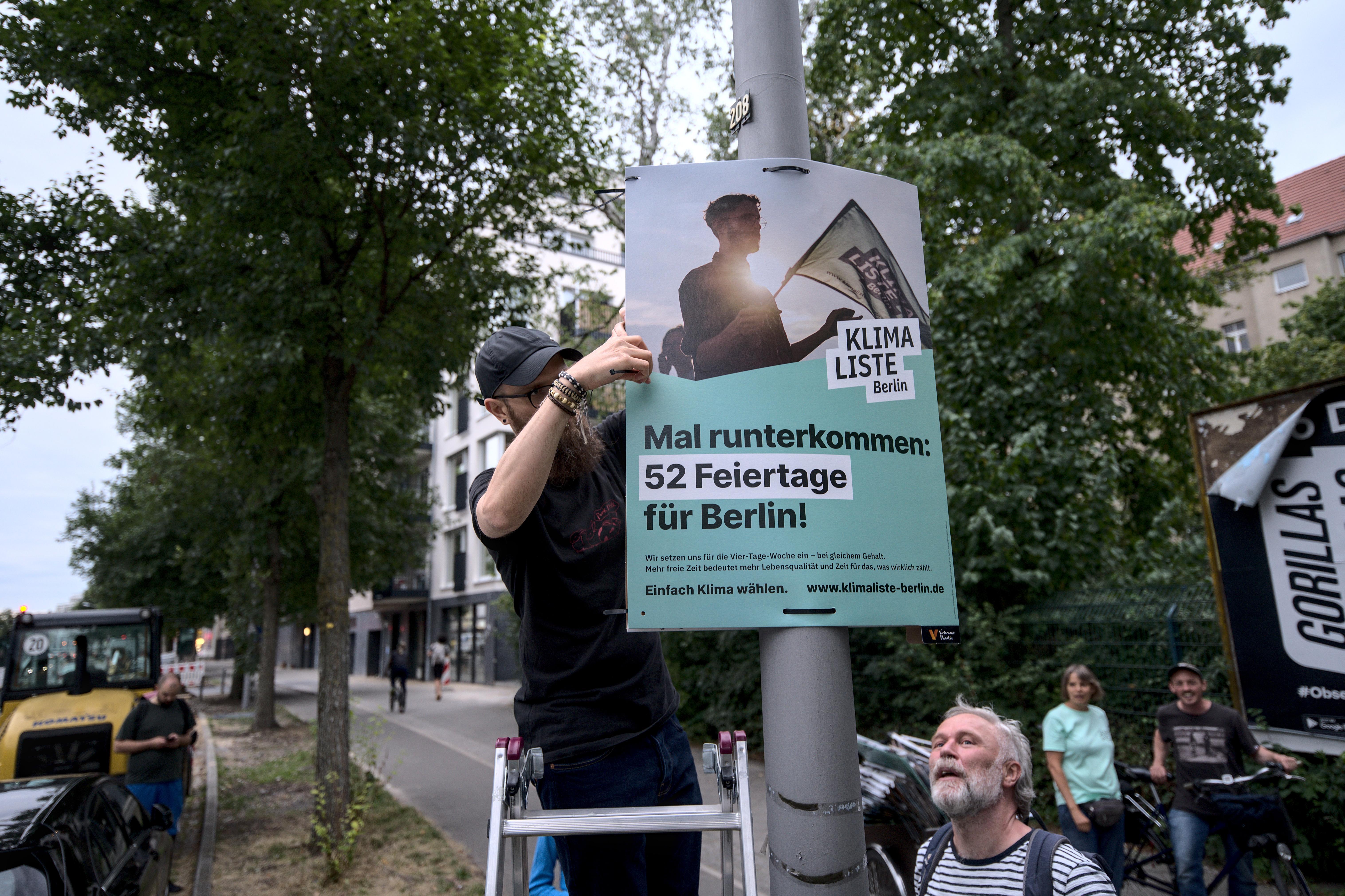 Aktivist:innen der Klimaliste Berlin hängen ein Wahlplakat auf